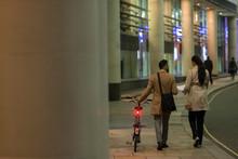 Business People With Bicycle Walking On Urban Sidewalk At Night