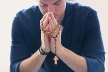 Serene Man Praying With Rosary