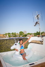 Portrait Playful, Carefree Young Woman In Bikini On Inflatable Pegasus In Sunny Rooftop Hot Tub
