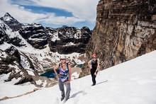 Female Hikers Hiking Snowy Mou...