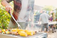 Man Barbecuing Corn, Sausage And Vegetable Kebabs
