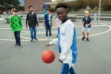 Portrait Confident Tween Boy Playing Basketball In Schoolyard