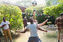 Male Friends Playing Soccer, Enjoying Backyard Summer Barbecue