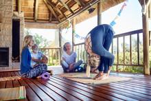 Female Yoga Instructor Demonstrating Forward Fold In Hut During Yoga Retreat