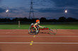 Teenage girl paraplegic athlete in wheelchair race on sports track at night