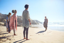 Woman Leading Yoga Class On Sunny Beach During Yoga Retreat