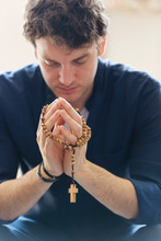 Serene Man Praying With Rosary