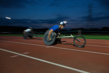 Determined Young Male Paraplegic Athlete Speeding Along Sports Track In Wheelchair Race At Night
