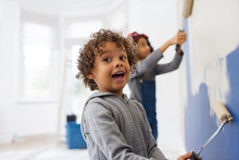 Portrait Cute, Playful Boy Painting Wall