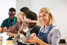 Portrait Confident Woman Making Clay Bowl In Art Class