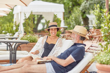 Mature Couple Reading Books, Relaxing On Lounge Chairs At Resort Poolside