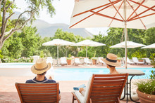 Couple Relaxing On Lounge Chairs At Sunny Resort Poolside