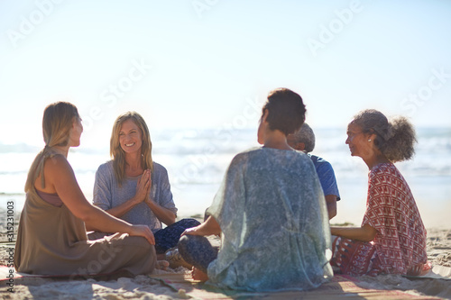 Happy friends talking in circle on sunny beach during yoga retreat - 315231003