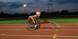 Determined teenage girl paraplegic athlete speeding along sports track in wheelchair race