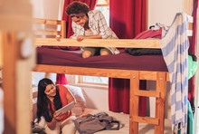 Young Female Backpackers On Bunk Bed In Youth Hostel