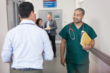 Smiling Male Surgeon Greeting Passing Doctor In Hospital Corridor