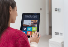 Woman Using Smart Home Automation System With Digital Tablet