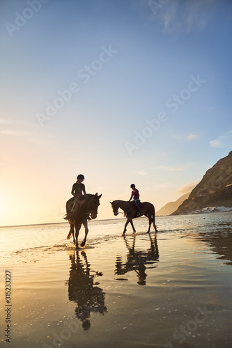 Young women horseback riding on tranquil sunset beach - 315233227