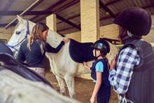 Female Instructor Helping Girls Prepare For Horseback Riding
