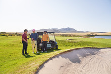 Male Golfer Friends Talking At Sand Trap On Sunny Golf Course