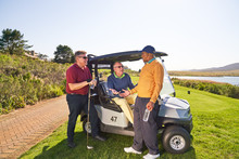 Male Golfer Friends Talking At Sunny Golf Cart