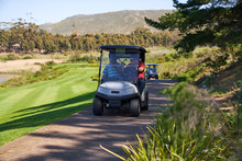 Male Golfers Riding In Golf Cart On Sunny Golf Course Path