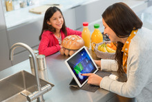 Daughter Watching Mother Using Digital Tablet In Kitchen