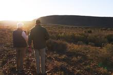 Men On Safari Watching Elephants In Sunny Grassland South Africa