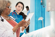 Female Doctor And Nurse Using Digital Tablet, Talking In Hospital Room