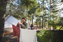 Man Hanging Laundry On Clothesline At Campsite In Woods