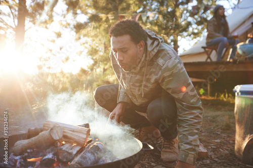 Man blowing on campfire in sunny woods - 315234674