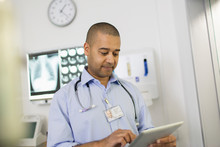 Male Doctor Using Digital Tablet In Hospital