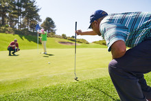 Male Golfer Preparing To Putt On Sunny Golf Course