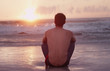 Pensive young man on beach watching sunset over ocean