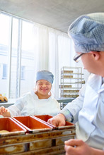 Happy Young Woman With Down Syndrome Baking In Kitchen