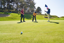 Male Golfer Friends Putting At Home On Sunny Golf Course
