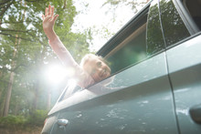 Carefree Girl With Arm Out Sunny Car Window