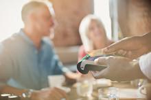 Close Up Waiter Using Credit Card Reader At Restaurant Table