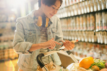 Young Woman With Headphones Using Cell Phone In Grocery Store Market