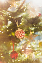 Red, White And Gold Ornaments Hanging From Christmas Tree