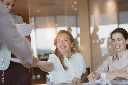 Photo Smiling businesswoman handing paperwork to colleague in conference room meeting