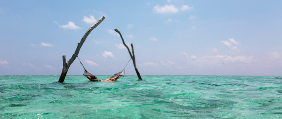 Young woman laying in hammock over tranquil blue ocean, Maldives, Indian Ocean