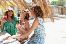 Happy Women Friends Drinking At Sunny Beach Bar
