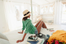 Woman Relaxing On Beach Hut Bed