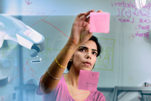 Focused Female Engineer Planning, Using Adhesive Notes In Office