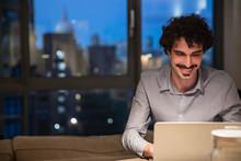 Man Using Laptop In Urban Apar...