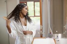 Beautiful Young Woman Brushing Hair In Bathroom Mirror