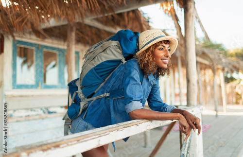 Happy young female backpacker on beach hut patio - 315249665