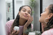 Beautiful Young Woman Applying Moisturizer In Bathroom Mirror