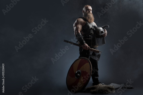 Leinwand Poster Medieval warrior berserk Viking with tattoo with axes attacks enemy